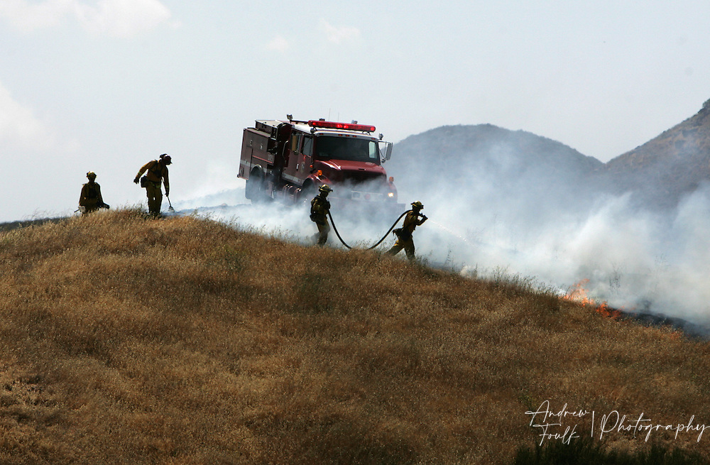 /Andrew Foulk/ For the Californian/.Cal Fire fire fighters are followed by a water truck as they douse flames on a ridge just west of Winchester road. The brush fire started at around 2pm in French Valley, just North of Keller Road and South of Scott Road. The Fire consumed an estimated 200 acres and caused the closure of Scott, and Winchester Roads.