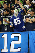 A fan sports a painted face and a team colored bald head as he cheers for the team during the Seattle Seahawks NFL week 19 NFC Divisional Playoff football game against the Carolina Panthers on Saturday, Jan. 10, 2015 in Seattle. The Seahawks won the game 31-17. ©Paul Anthony Spinelli