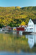 Colourful Solvorn dockhouses reflected in Lustra Fjord, Vestlandet, Norway