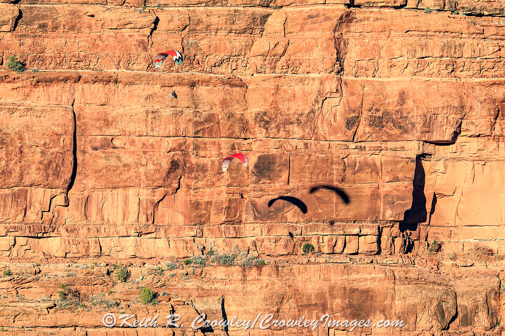 Two visitors fly motorized parachutes in a scenic area outside of Monument Valley.