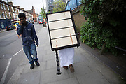 Man carrying a small piece of furniture on his head in West London, United Kingdom.