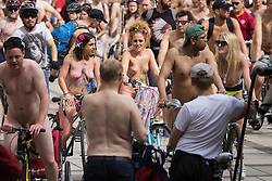 Westminster Bridge, London, June 11th 2016. Hundreds of naked and semi-naked cyclists participate in the World Naked Bike Ride that takes place in cities around the world, to highlight the alternatives to hydrocarbon fuels. PICTURED: Cyclists move off after a break to allow stragglers to catch up with them.