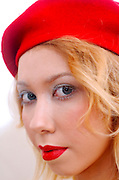 blond model in her 20s with white makeup red lips and red beret imitating christmas colours