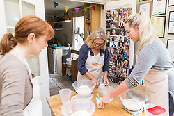 Baker Liz Wilson leads a class with participants Hazel Griffiths, left and Jess Hayden, right,  learn a number of baking methods at her Fulham home in London. London, August 16 2019.