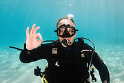 Underwater Hand signs scuba diver demonstrates the sign language for divers. Are you OK? or I am OK! A circle is made with thumb and forefinger, extending the remaining fingers