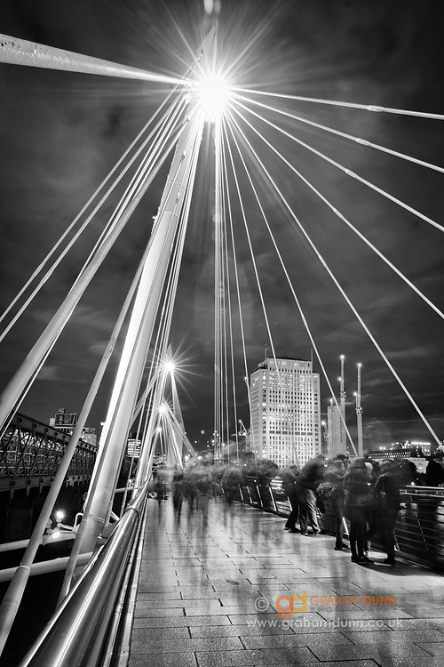 Anonymous figures enjoy the view whilst moving across the Golden Jubilee Footbridge in London. Night cityscape / urban photography in England's capital city, UK.