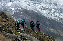 © Licensed to London News Pictures. 30/01/2016. Snowdonia National Park, Gwynedd, Wales, UK. Climbers set off at the start of The Pyg Track route up Mount Snowdon from the car park at Pen-Y-Pass. After a mild spell, temperatures dropped to around zero this morning in Snowdonia National Park. A dusting of snow covers the peaks and there is a strong Westerly wind giving a much lower 'feels like' temperature.Photo credit: Graham M. Lawrence/LNP