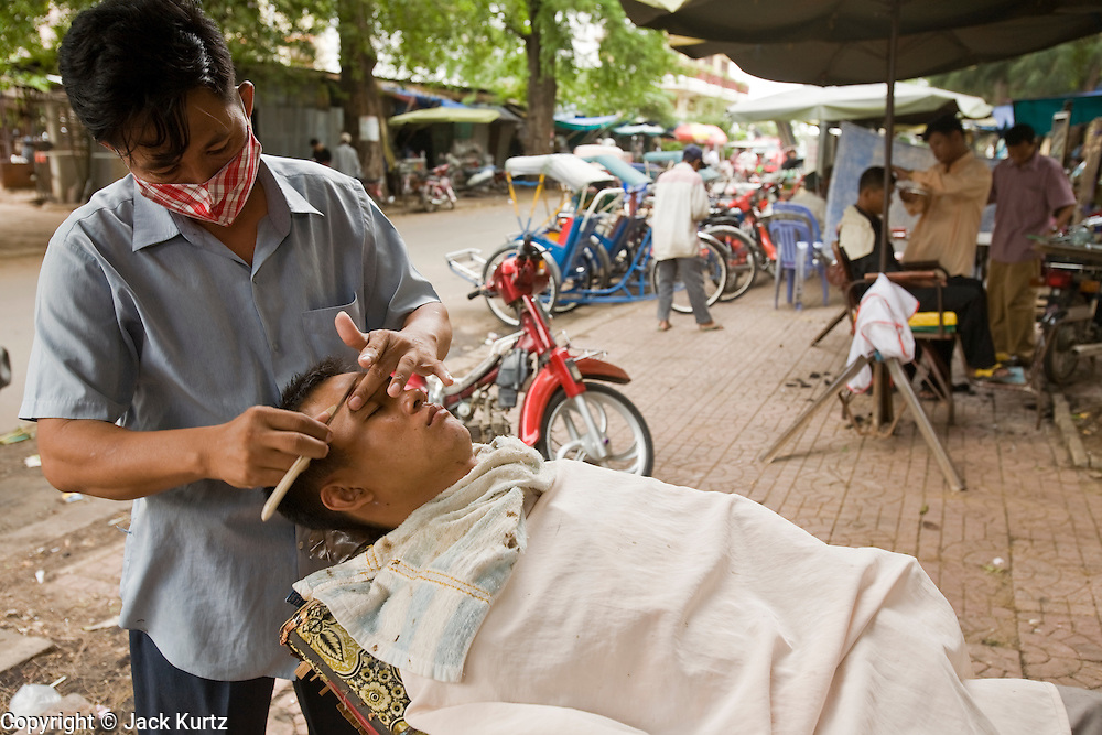29 JUNE 2006 - PHNOM PENH, CAMBODIA: A barber cuts a client's hair at an outdoor barbershop in a sidewalk in centeral Phnom Penh, Cambodia. PHOTO BY JACK KURTZ