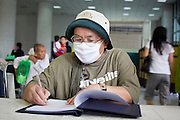Sept. 22, 2009 -- BANGKOK, THAILAND:  A woman wearing a breathing mask for protection from H1N1 flu virus signs a get well note in the lobby of Siriraj Hospital for King Bhumibol Adulyadej, the 81-year-old King of Thailand. The King has been admitted to hospital suffering from a fever. Doctors at Siriraj Hospital said the world's longest-serving monarch, had shown signs of fatigue and was being treated with antibiotics. King Bhumibol is deeply revered by most Thais and his health is a matter of public anxiety. His Majesty was admitted on Saturday suffering from a fever, fatigue and loss of appetite. Doctors continued to treat the King with intravenous drips and antibiotics, hospital officials said. More than 3,500 people have come to the hospital to pray for the King's speedy recovery and to sign get well cards for him.  Photo by Jack Kurtz