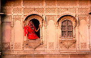 INDIA, RAJASTHAN a young woman in the carved window of her  home in the ancient city of Jaisalmer, in  the Great Thar Desert