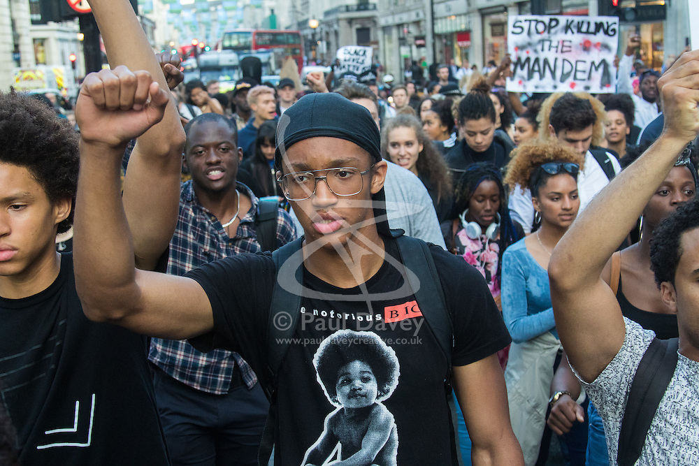 """London, July 8th 2016. Hundreds gather on London's Southbank before marching through the streets of London to Parliament Square, Downing Street and the BBC, in a Black Lives Matter protest in solidarity with Americans following the shooting dead of two black men, Philando Castile in Minnesota and Alton Sterling in Louisiana by police in the US. PICTURED: The crowd stops in Oxford Circus, chanting and singing """"All I really know is they don't really care about us""""."""