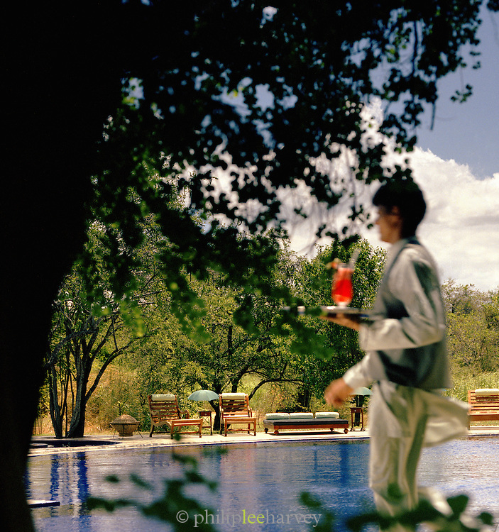 A waiter serves cocktails by the swimming pool of a hotel in Sri Lanka