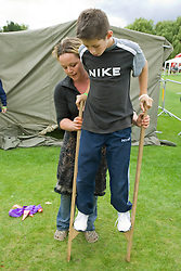 Circus skills play worker showing a boy how to use stilts at a Parklife summer activities event,