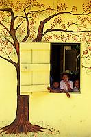 Belize. San Pedro Columbia.<br /> Niños se asoman a la ventana junto al mural de su colegio en San Pedro Columbia.<br /> <br /> © JOAN COSTA