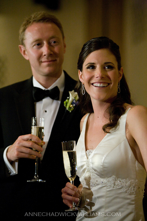A bride and groom are toasted at their wedding reception at the Sutter Club in Sacramento, California.