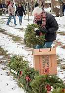 Goshen, New York - A man carries wreaths to graves during a Wreaths Across America ceremony at Orange County Veterans Memorial Cemetery on Dec. 16, 2017. About 3,000 wreaths were placed at graves, and small American flags were added to the wreaths at veterans' graves.