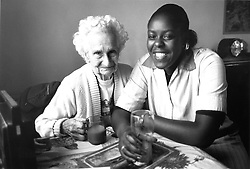 Female carer with elderly woman sitting at table laughing,