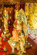 """16 DECEMBER 2012 - SINGAPORE, SINGAPORE: Buddhas in the main prayer hall at the Buddha Tooth Relic Temple and Museum in the Chinatown section of Singapore. The temple houses a sacred Buddha tooth relic. It is a """"Mahayana"""" Buddhist temple, the larger of the two Buddhist sects. Mahayana Buddhism is practiced in India, China, Vietnam (northern), Japan, Tibet, Mongolia, Korea and in Chinese immigrant communities around the world.      PHOTO BY JACK KURTZ"""