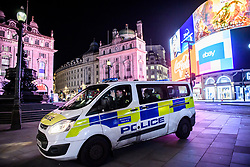 © Licensed to London News Pictures. 20/03/2020. London, UK. Police mount the pavement at Piccadilly Circus without a pedestrian in sight  before moving on. The West End was left unprecedentedly empty on Friday night following the government's announcement that all bars, pubs and restaurants must be closed immediately in the latest step to curb the coronavirus outbreak.  Photo credit: Guilhem Baker/LNP
