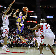 Nov 24, 2010; Houston, TX, USA; Golden State Warriors point guard Stephen Curry (30) shoots over Houston Rockets power forward Luis Scola (4) during the first quarter at the Toyota Center.  Mandatory Credit: Thomas Campbell-US PRESSWIRE