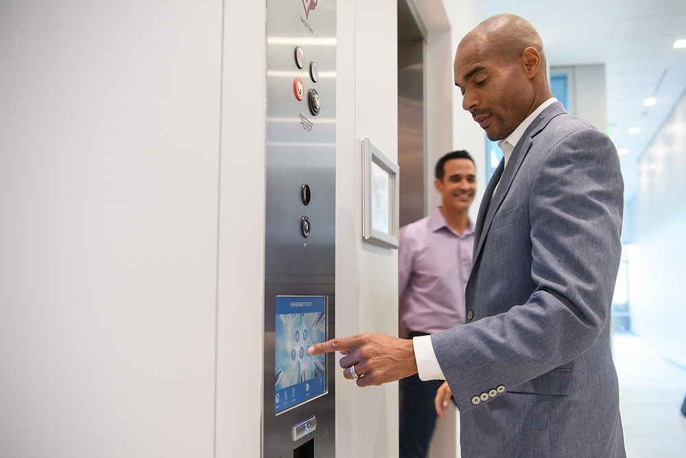 Man in business attire calling an elevator inside a corporate office. Part of a corporate reportage shoot for an international brand.