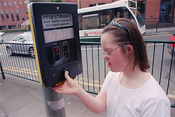 Teenage girl with Downs Syndrome pushing button at pedestrian crossing,