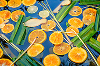 Detail view of citrus, pandanus, lemongrass and ginger floating atop a healing bath, Fivelements, Bali. Spa photographer: Djuna Ivereigh.