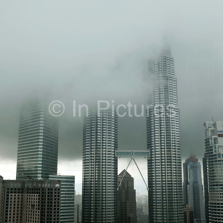 Mist coming down over the Petronas Towers (also known as the Petronas Twin Towers), a landmark of Kuala Lumpur, Malaysia during monsoon season. The 88-floor towers were designed by Argentine American architect César Pelli and are constructed largely of reinforced concrete, with a steel and glass facade designed to resemble motifs found in Islamic art, a reflection of Malaysia's Muslim religion. According to the Council on Tall Buildings and Urban Habitat (CTBUH)'s official definition and ranking, they were the tallest buildings in the world from 1998 to 2004 and remain the tallest twin towers in the world replacing World Trade Center in New York.