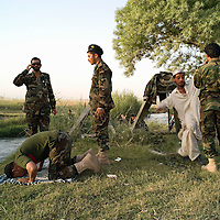Afghan National Army troops, relax, pray and picnc on the riverbank as refugees from the recent fighing with the Taliban return to their homes. Arghandab district, Kandahar, Afghanistan on the 20th June 2008.