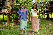 The wife and daughter of Along Sega, a hard fighting resistance fighter who died a decade before. The Penan native people are learning to live a sedentary lifestyle which includes living in wooden houses, farming and fishing. They were traditionally nomadic hunter-gatherers. These days they have become forcibly settled as their hunting grounds have been largely destroyed by logging concessions and palm-oil plantations. Limbang Sarawak Malaysia 2015<br /> <br /> There are only a few, difficult to find, scarce communities of semi-nomadic Penan nowadays, who live like of those of old, hidden away deep in the tropical forest, hunter-gathering, wearing loin cloth 'chawats', hunting wild boar with blowpipes and poison arrows, and extracting sago-root flour, their staple carbohydrate, by hand.<br /> <br /> Borneo native peoples and their rainforest habitat revisited two decades later: 1989/1991 and 2012/2014/2015. <br /> <br /> Sarawak's primary rainforests have been systematically logged over decades, threatening the sustainable lifestyle of its indigenous peoples who relied on nomadic hunter-gathering and rotational slash & burn cultivation of small areas of forest to survive. Now only a few areas of pristine rainforest remain; for the Dayaks and Penan this spells disaster, a rapidly disappearing way of life, forced re-settlement, many becoming wage-slaves. Large and medium size tree trunks have been sawn down and dragged out by bulldozers, leaving destruction in their midst, and for the most part a primary rainforest ecosystem beyond repair. Nowadays palm oil plantations and hydro-electric dam projects cover hundreds of thousands of hectares of what was the world's oldest rainforest ecosystem which had some of the highest rates of flora and fauna endemism, species found there and nowhere else on Earth, and this deforestation has done irreparable ecological damage to that region