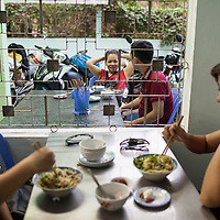 Diners enjoy  bowls of  bún thịt nướng in the popular restaurant Huyền Anh in Hue, Vietnam. Bún thịt nướng is a cold rice noodle dish topped with fresh herbs, vegetables, grilled pork and peanuts and served with a side of a sweet, vinegary, fish sauce-based dipping sauce infused with garlic and peppers.