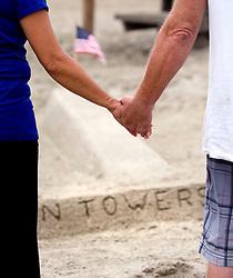 Sept. 11, 2012 - San Clemente, California, U.S. - Beachgoers hold a vigil near San Clemente artist Jay Bellamy's sand sculpture of the Twin Towers on a dreary Tuesday. (Credit Image: © H. Lorren Au Jr/The Orange County Register/ZUMAPRESS.com)