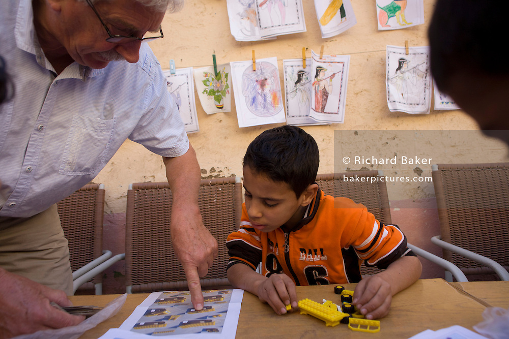 A local boy gets help to make a Lego model from a Belgian teaching volunteer at the American-sponsored Theban Mapping Project Library on the West Bank of Luxor, Nile Valley, Egypt. The Theban Mapping Project's goal is to enable local people to have a place where they can read and learn. The organisation is run by American Egyptologist Dr Kent Weeks who is committed to the original goal of accurately documenting the archaeological heritage of Thebes