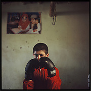 A boy exercises boxing in a gym in the outskirts of Kabul.