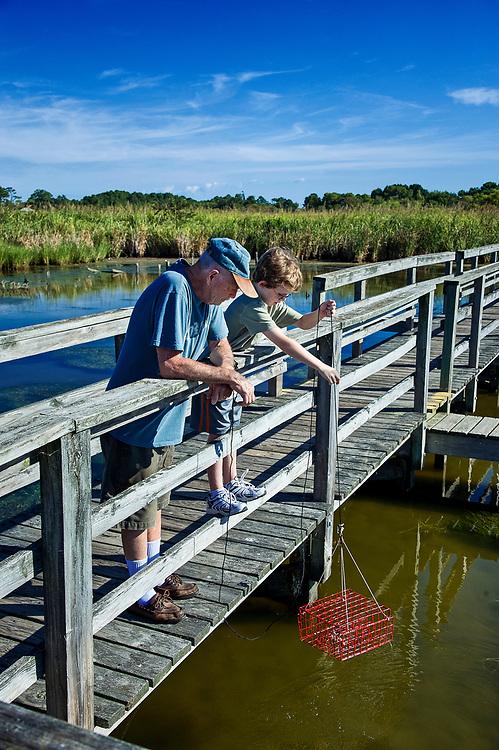 Grandfather and boy crabbing from a dock, Outer Banks, North Carolina, USA.