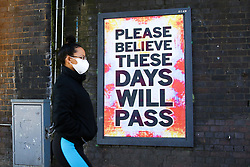© Licensed to London News Pictures. 05/04/2020. London, UK. A woman wearing a face mask walks past 'PLEASE BELIEVE THESE DAYS WILL PASS' sign in north London during a pandemic outbreak of the coronavirus. Photo credit: Dinendra Haria/LNP