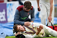 Eddie Byrom of Somerset has his dislocated shoulder put back in its socket by the physio during the Specsavers County Champ Div 1 match between Somerset County Cricket Club and Worcestershire County Cricket Club at the Cooper Associates County Ground, Taunton, United Kingdom on 22 April 2018. Picture by Graham Hunt.