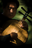 A man playing a yueqin, also called a moon guitar, in Taoranting park park in Beijing, China. Musicians come to the park to practice Beijing opera.
