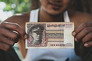 Bagan, Myanmar - November 14, 2011: A man holds an old ten-kyat note featuring a portrait of General Aung San, considered the Father of the Nation of modern Myanmar. Assassinated in 1947, just six months before Burmese independence from the British, he is the father of Aung San Suu Kyi.