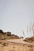 Women walking by sand dunes in Spain