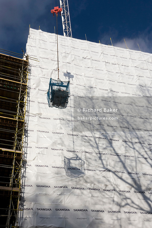 Crane lifts a load of construction materials high above London street where a Skanska building project is underway.