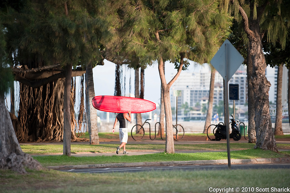 A surfer walking through Waikiki with his surfboard on his shoulder.