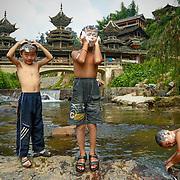Children bath in the river running through Dimen.