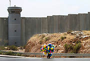 A Palestinian peddler is walking past a guard tower and the Israeli separation barrier near Hizme checkpoint, northern Jerusalem. 2013