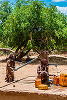 Hamer tribe people pumping water from a well, Omo Valley, Ethiopia.