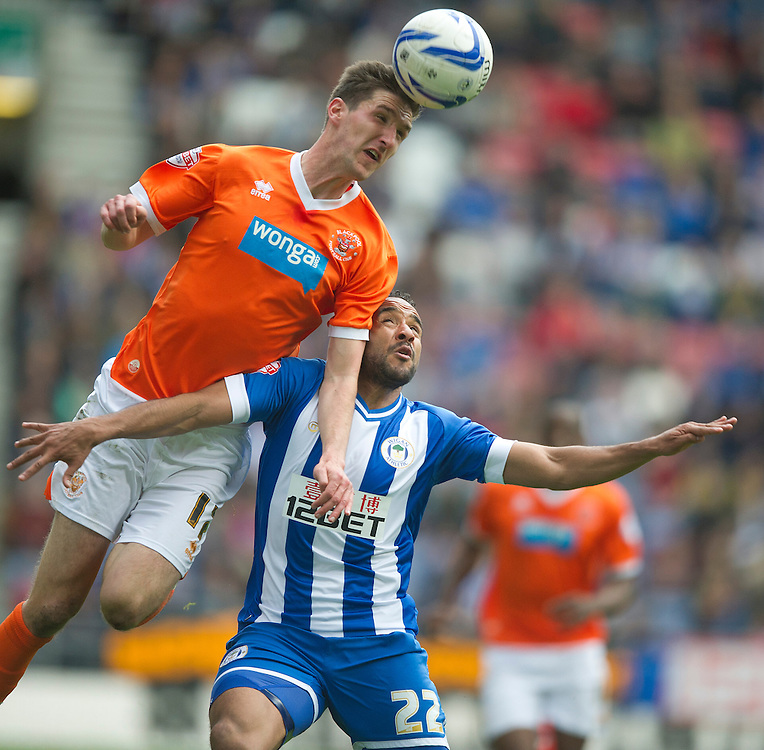 Blackpool's Chris Basham and Wigan Athletic's Jean Beausejour<br /> <br /> Photo by Stephen White/CameraSport<br /> <br /> Football - The Football League Sky Bet Championship - Wigan Athletic v Blackpool - Saturday 26th April 2014 - DW stadium - Wigan<br /> <br /> © CameraSport - 43 Linden Ave. Countesthorpe. Leicester. England. LE8 5PG - Tel: +44 (0) 116 277 4147 - admin@camerasport.com - www.camerasport.com