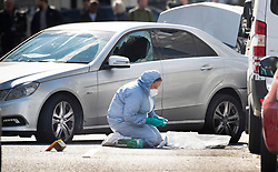 © Licensed to London News Pictures. 13/04/2019. London, UK. A police forensics officers works to gather evidence next to a car with a smashed window in Holland Park after shots were fired by police near the Ukranian embassy. Photo credit: Peter Macdiarmid/LNP