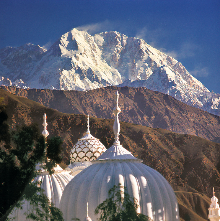 The white domes of Chitral Mosque point upward to the 25,289' summit of Tirich Mir, the highest mountain in Pakistan's Hindu Kush Range, some 50 miles in the distance.