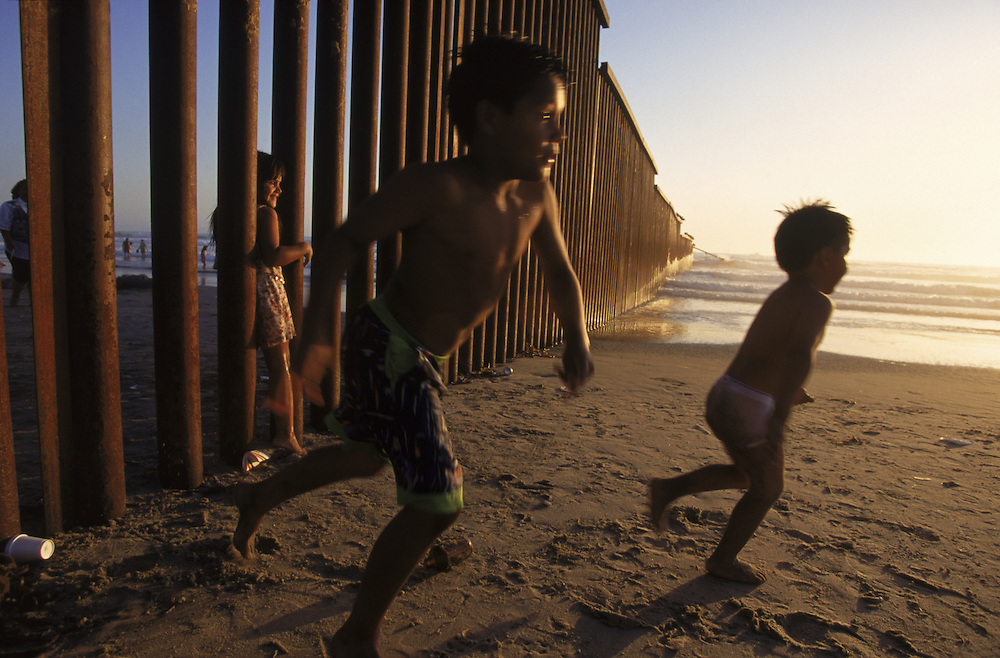 This fence divides the city of Tijuana from San Diego and is a popular gathering spot for undocumented migrants attempting a quick entry into the US. Kids play between the two worlds by darting onto the U.S. side of the fence. Please contact Todd Bigelow directly with your licensing requests.