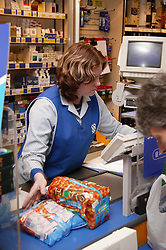 Shop assistant with learning disability serving customer at supermarket checkout,